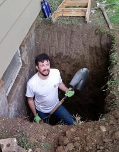 Frank digging a hole with a shovel and pick.